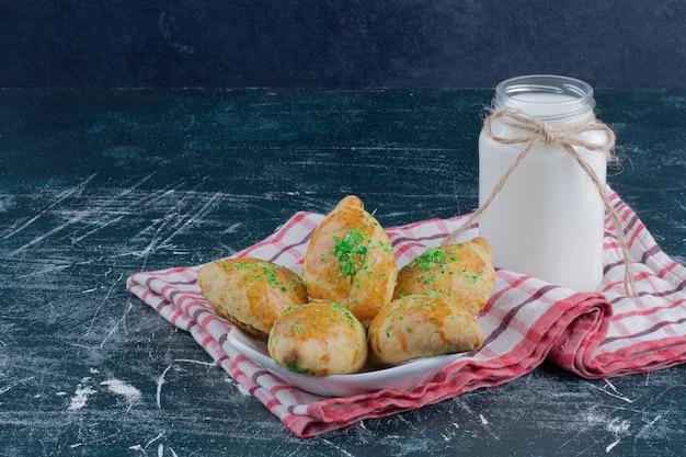 Prato de biscoitos caseiros e pote de leite na mesa de mármore.