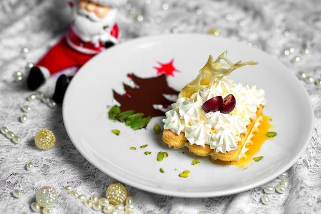 Prato de biscoitos com creme ao lado da árvore de natal em pó de café