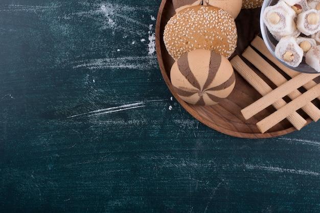 Prato de biscoitos com pãezinhos, lokum em um copo de vidro e waffles no canto superior