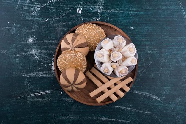 Prato de biscoitos com pãezinhos, lokum em um copo de vidro e waffles no centro