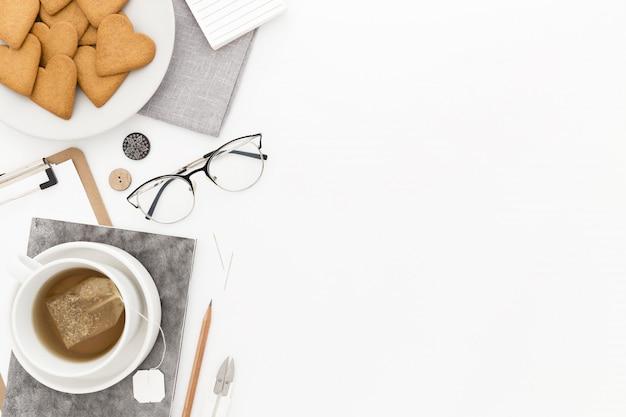 Prato de biscoitos, copos, uma xícara de chá e alguns papéis em uma superfície branca