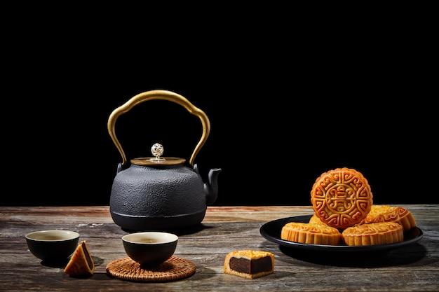 Prato de biscoitos deliciosos e um bule de chá em uma superfície de madeira