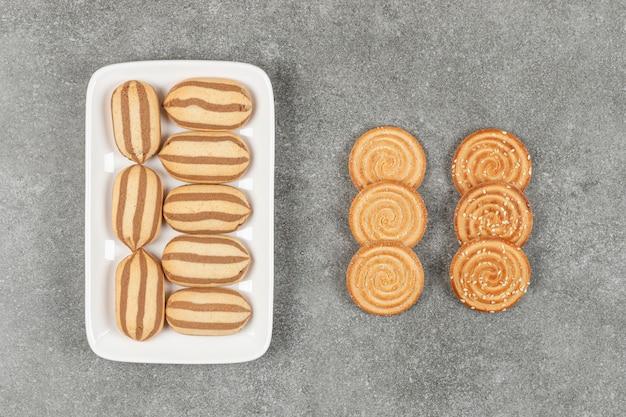 Prato de biscoitos e biscoitos listrados de chocolate na superfície de mármore