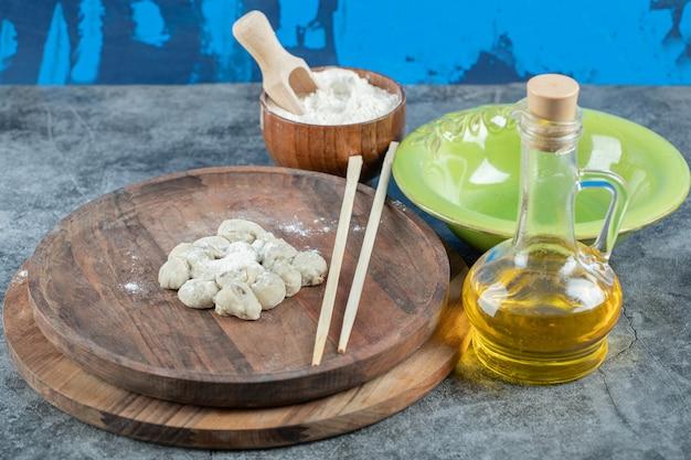 Prato de bolinho de massa com tigela de farinha e azeitona na mesa de mármore.