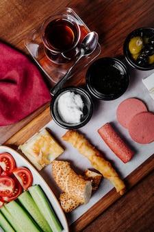 Prato de café da manhã com comidas mistas, um copo de chá preto e variedade de pães.