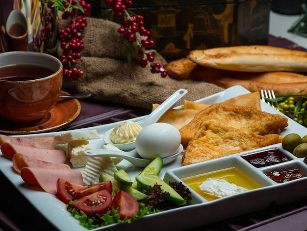 Prato de café da manhã com ingredientes misturados e chá