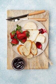 Prato de café da manhã com queijo, pão, morangos e geleia
