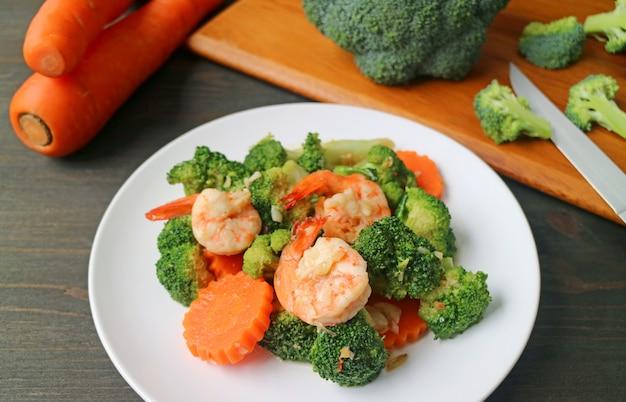 Prato de camarão frito com brócolis e cenoura com legumes cortados embaçados