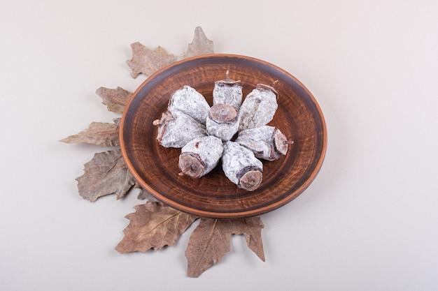 Prato de caquis secos e folhas secas em fundo branco. foto de alta qualidade