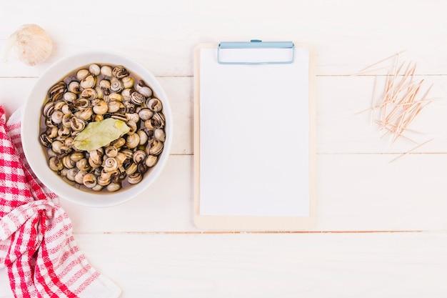 Prato de caracol e prancheta na mesa da cozinha