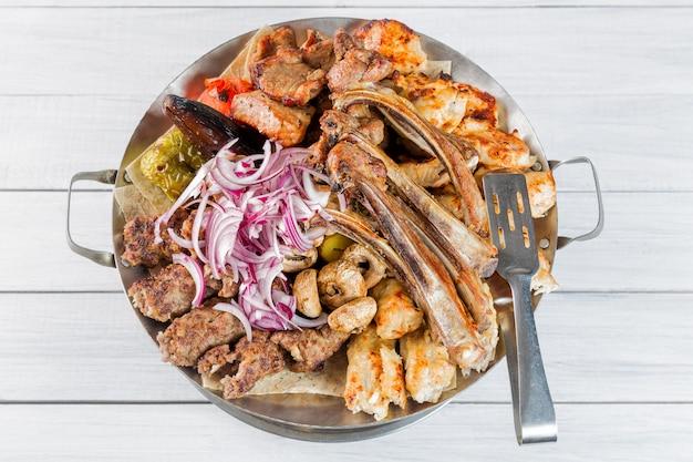 Prato de carne com deliciosos pedaços de carne, costelas, batatas grelhadas e cogumelos com cebola.