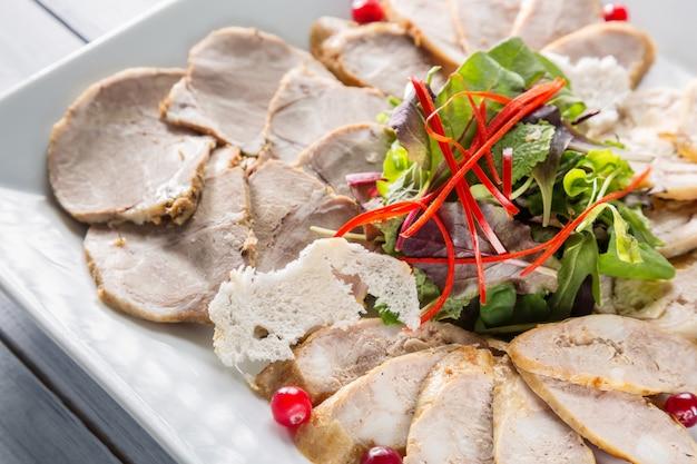 Prato de carne com deliciosos pedaços de presunto fatiado, ervas e carne com cranberry