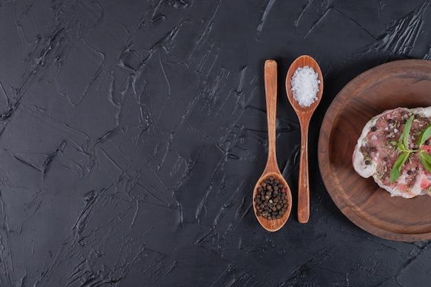 Prato de carne crua decorado com hortelã fresca e colheres de especiarias em fundo escuro.