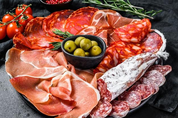 Prato de carne curada de tapas espanholas tradicionais. chouriço, jamon serrano, lomo e fuet. fundo preto. vista do topo.