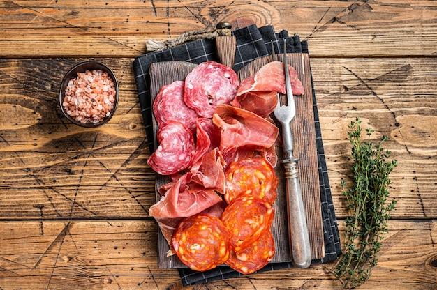 Prato de carne curada servido como tapas espanholas tradicionais. salame, jamon, salsichas choriso em uma placa de madeira. fundo de madeira. vista do topo.