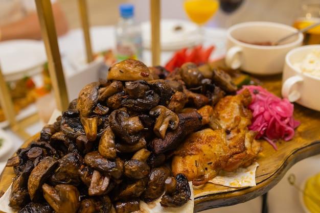 Prato de carne frito no carvão com especiarias em uma prateleira de madeira de carne de porco kebab de cogumelo de frango ...