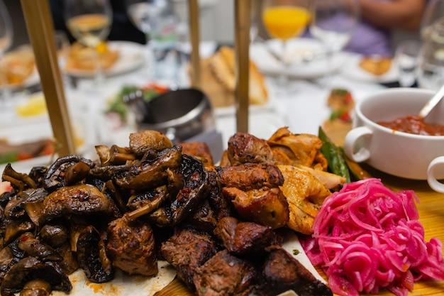 Prato de carne frito no carvão com especiarias em uma prateleira de madeira de carne de porco kebab de cogumelo de frango.
