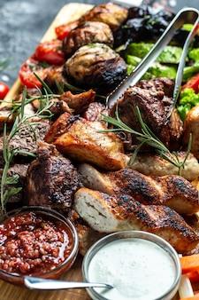 Prato de carne grelhada mista. carnes e vegetais grelhados. imagem vertical. vista do topo.