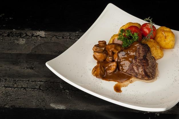 Prato de carne numa superfície de madeira velha. carne frita com batatas em um prato branco sobre uma velha placa de madeira