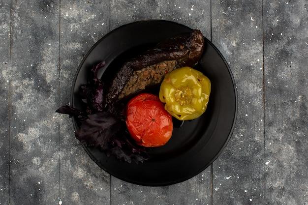 Prato de carne oriental dolma com berinjela de tomate assado e pimentão verde com carne picada dentro de chapa preta