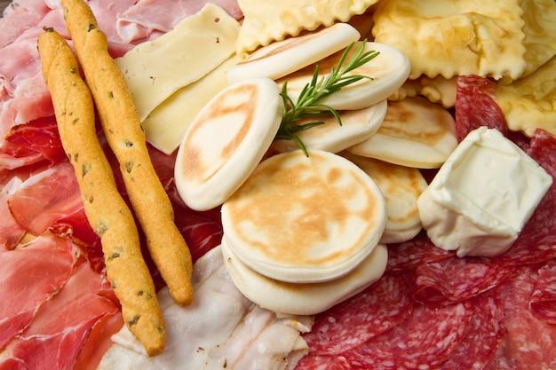 Prato de carnes curadas, queijos e bolinho frito