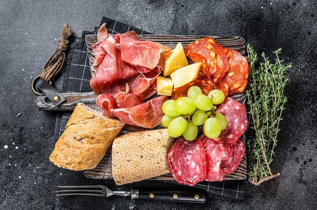 Prato de carnes frias, charcutaria - tapas tradicionais espanholas em uma placa de madeira com pão e uva. fundo preto. vista do topo.