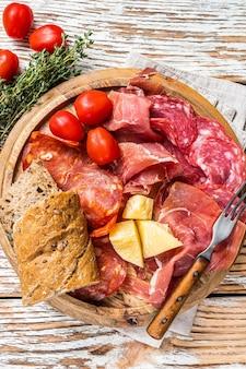 Prato de carnes frias, tapas tradicionais espanholas de charcutaria em uma placa de madeira. fundo de madeira branco. vista do topo.