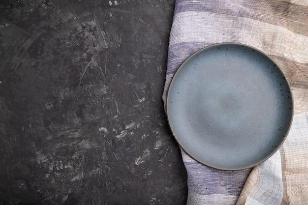 Prato de cerâmica azul vazio sobre fundo de concreto preto e têxteis de linho. vista superior, configuração plana.