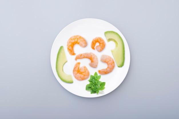 Prato de cerâmica branca com frutos do mar camarão cozido abacate