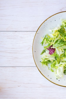 Prato de cerâmica branca com salada fresca na superfície de madeira
