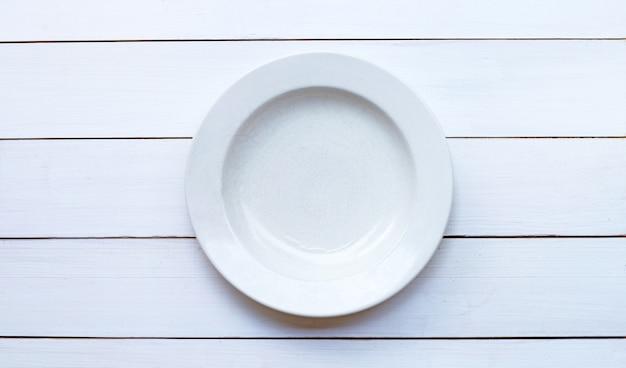 Prato de cerâmica branco vazio no isolado de madeira branco. copie o espaço