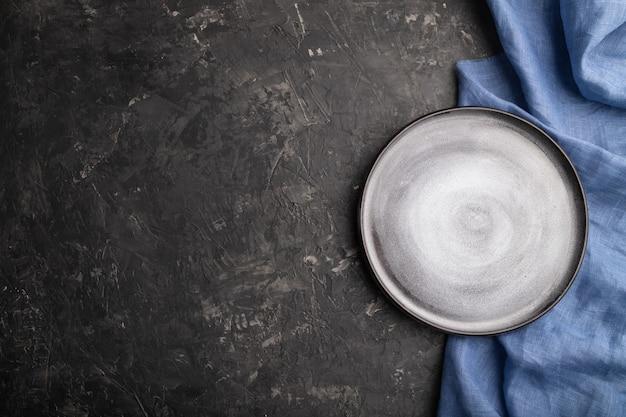 Prato de cerâmica cinza vazio sobre fundo preto de concreto e têxteis de linho azul. vista do topo,