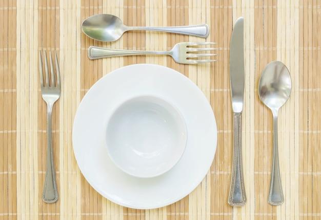 Prato de cerâmica closeup com garfo de aço inoxidável e colher e faca na mesa de jantar