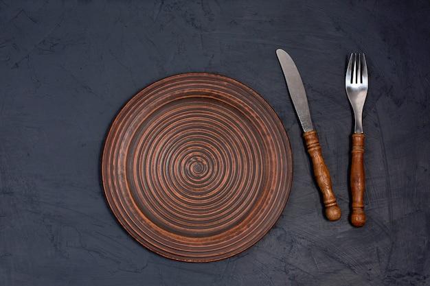 Prato de cerâmica marrom com garfo e faca em uma mesa preta