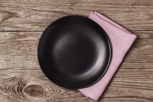 Prato de cerâmica preta vazio com guardanapo em uma mesa de madeira
