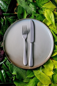 Prato de cerâmica vazio com faca e garfo em fundo feito de folhas verdes, gradiente verde. lugar vazio para o produto. conceito de comida eco de menu de verão. layout criativo da natureza, vista superior, disposição plana