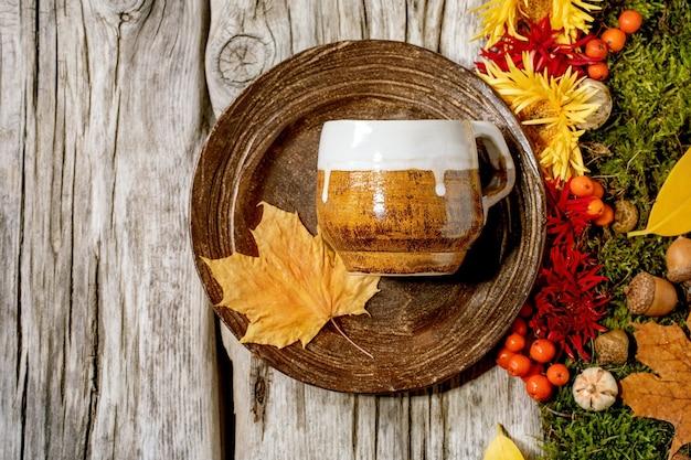 Prato de cerâmica vazio e caneca na velha mesa de madeira decorada com folhas amarelas de outono, frutos de outono, musgo e flores