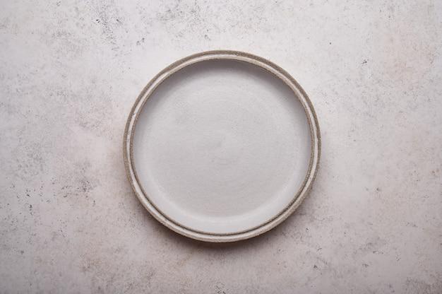Prato de cerâmica vazio na mesa de concreto claro fundo cópia espaço menu receita conceito vista superior plana
