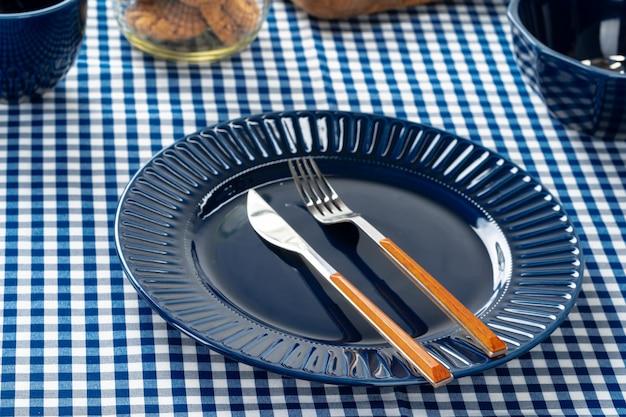 Prato de cerâmico azul profundo com talheres close-up na mesa