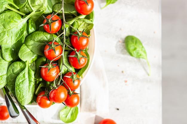 Prato de cerâmico branco com espinafre e tomate cereja vermelho