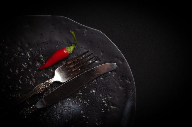 Prato de cerâmico redondo com padrão de círculos, garfo vintage e pimenta fresca vermelha em fundo preto.
