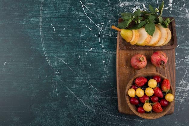Prato de cereja com romã e peras em uma travessa de madeira do lado direito