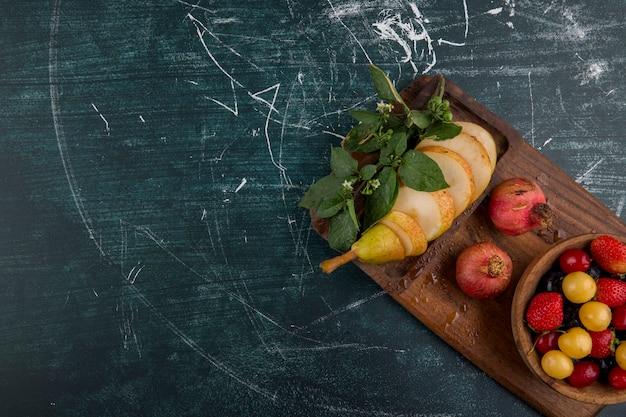 Prato de cereja com romã e peras em uma travessa de madeira no canto