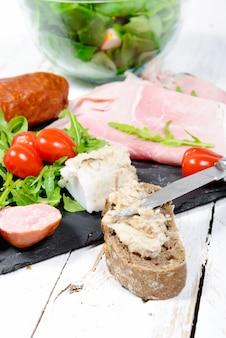 Prato de charcutaria com pão e tomate na placa de madeira