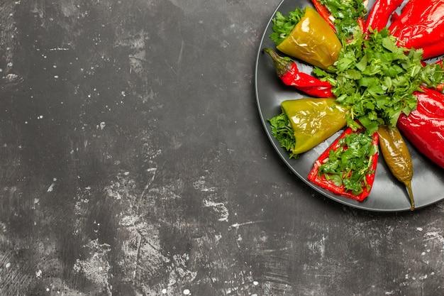 Prato de close-up com pimentas vermelhas e verdes com ervas na mesa