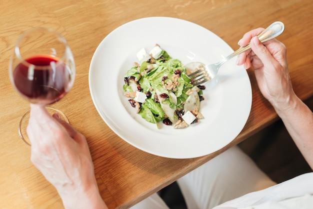 Prato de close-up com salada e vinho na mesa de madeira