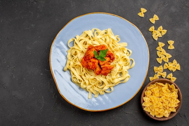 Prato de close-up de macarrão prato azul de macarrão apetitoso com molho e carne ao lado do prato de macarrão na mesa escura