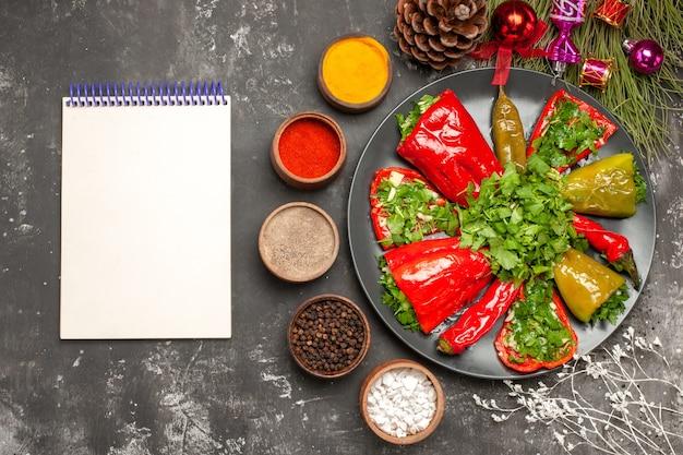 Prato de close-up superior com pimentas pimentas com ervas, caderno branco, cones, especiarias, brinquedos de natal