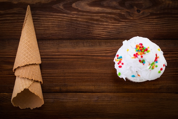 Prato de colher de sorvete de baunilha swith granulado e cones de waffle em fundo de madeira com espaço de cópia.