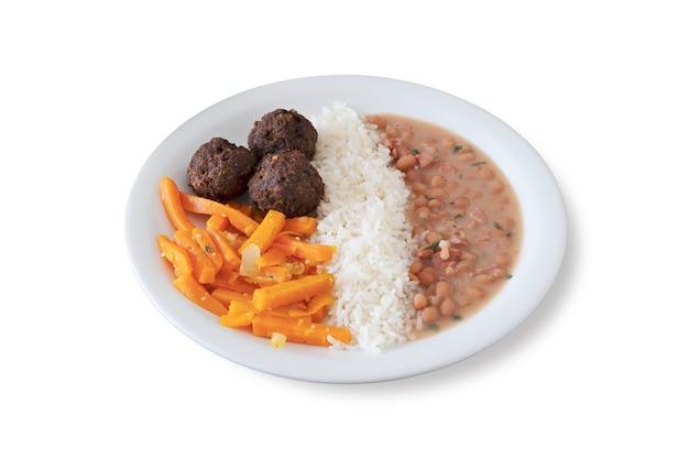 Prato de comida brasileira com almôndegas, cenouras, arroz e feijão. fundo branco.